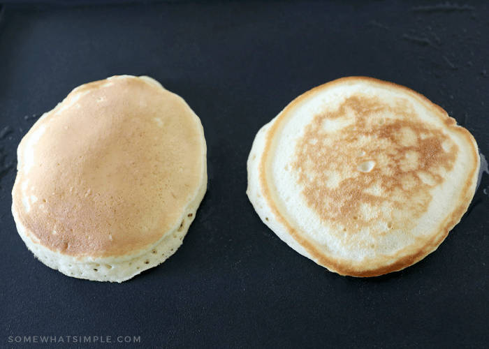 two pancakes side by side on a black griddle