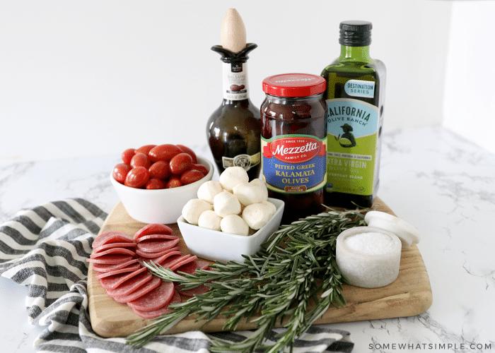 ingredients to make caprese skewers on a wood cutting board