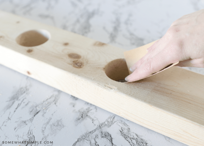 sanding a piece of wood with holes drilled into it