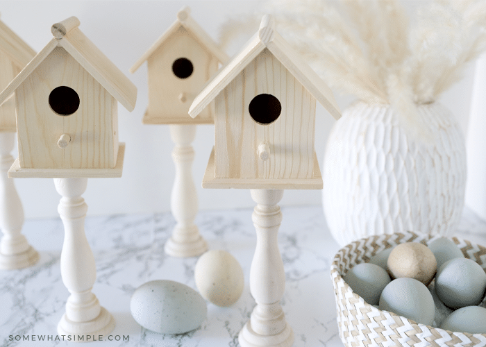 4 wood birdhouses on a white counter next to a basket of easter eggs