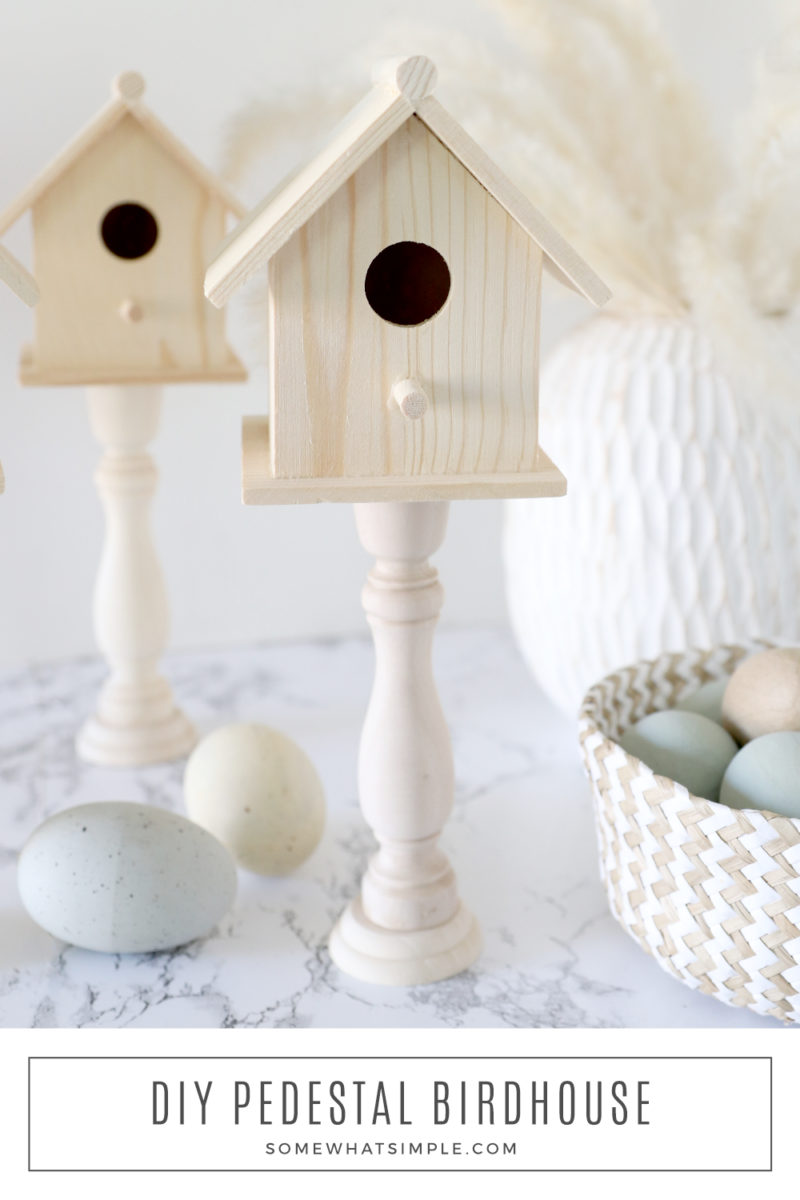 2 wood birdhouses next to a basket of easter eggs