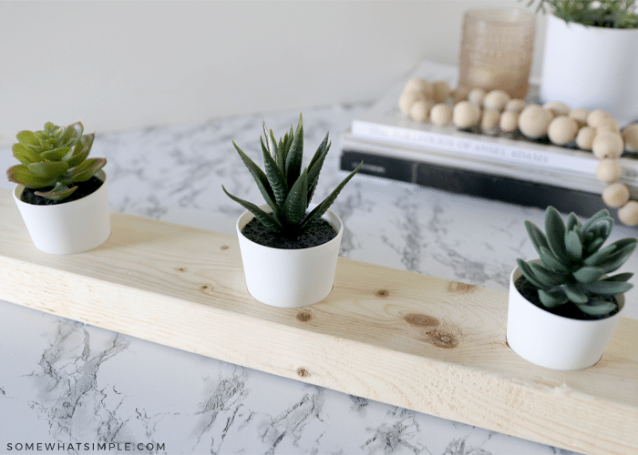 three faux succulents in a wood board