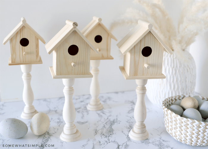 4 wood birdhouses with a basket of eggs on the side