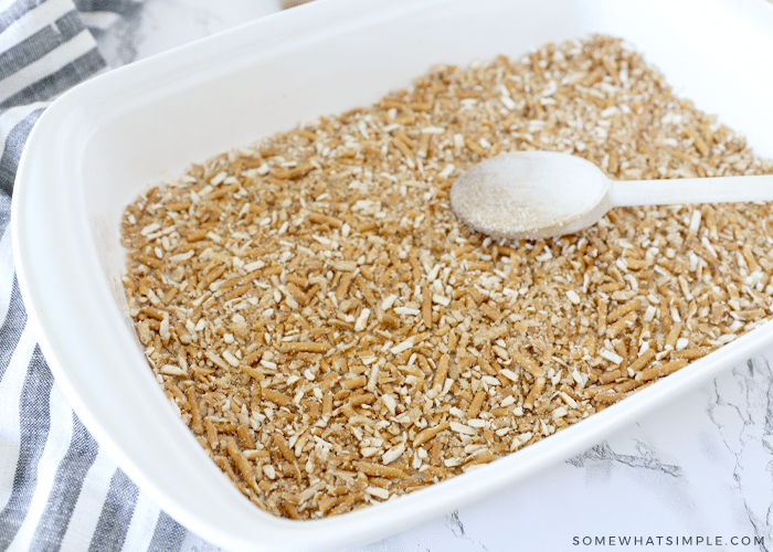 pressing pretzel crumbs into a baking pan with a wooden spoon