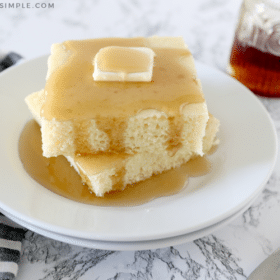 sheet pan pancakes topped with butter on a white plate covered in syrup