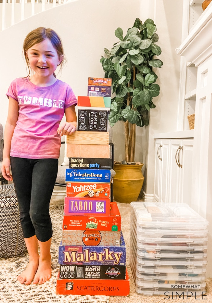 little girl standing next to a pile of board games