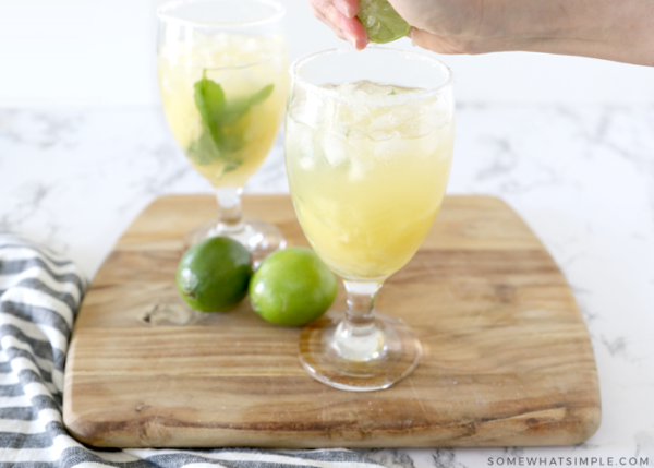 squeezing lime over a margarita
