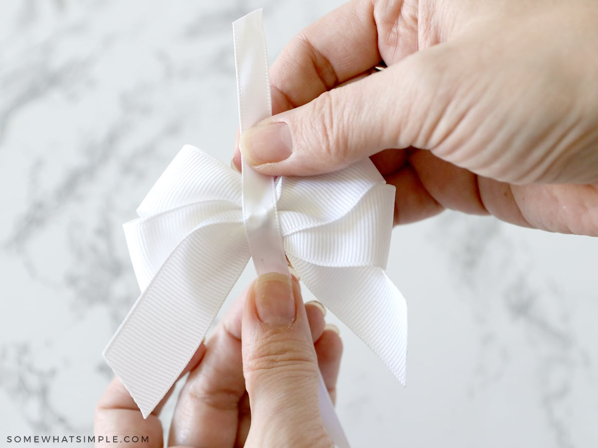 adding a ribbon to the center of a hair bow