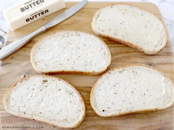 buttering each slice of bread for a sandwich