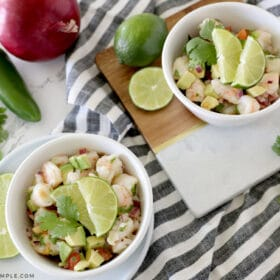 two small white bowls with avocado shrimp salad inside
