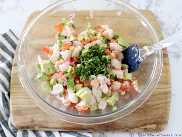mixing a shrimp avocado salad