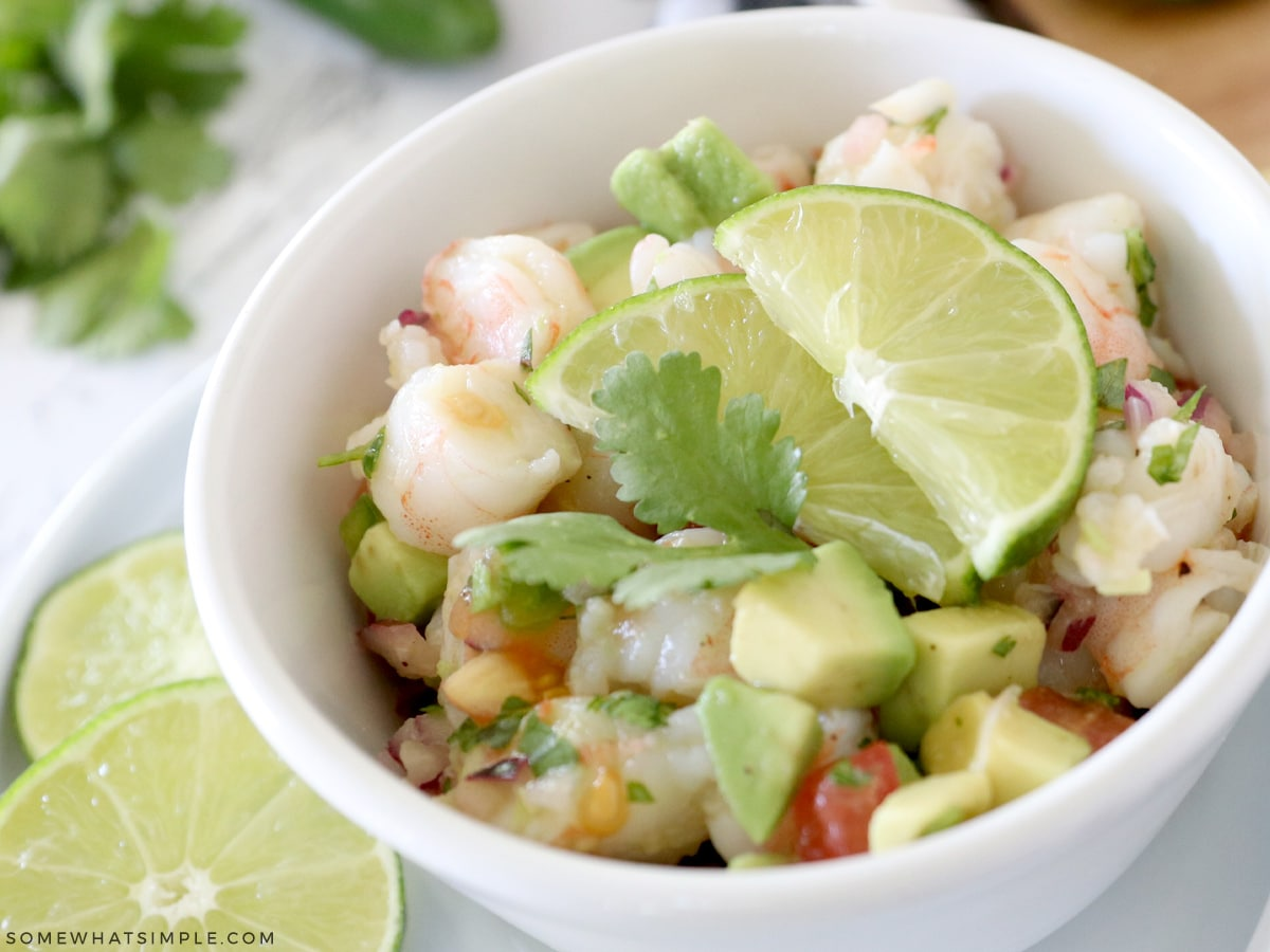 shrimp avocado salad in a white bowl with lime slices