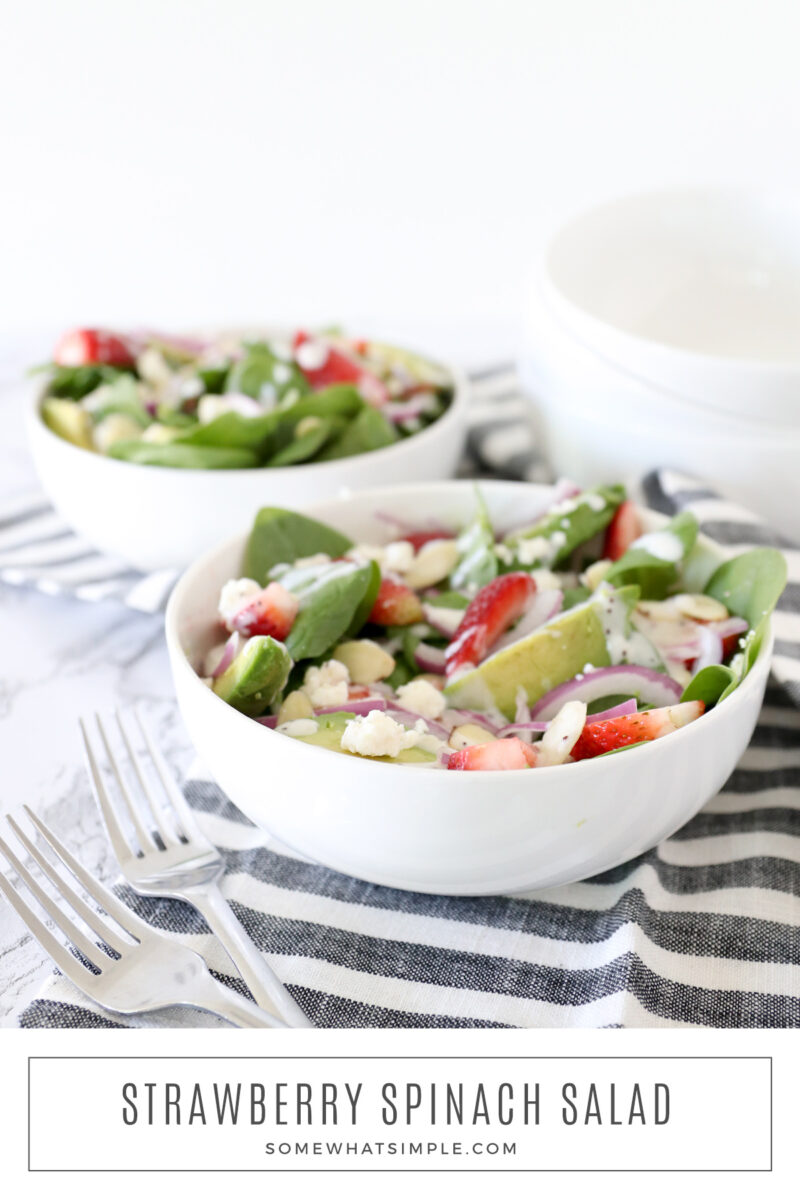 2 white bowls filled with strwberry spinach salad with avocado and red onion