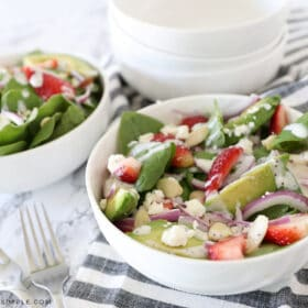white bowl with strawberry spinach salad