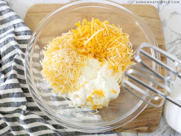 adding different cheeses to a bowl