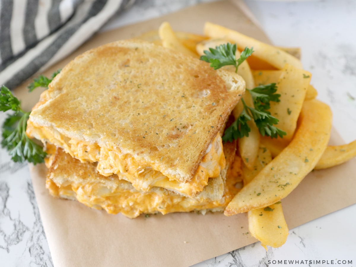 close up of a buffalo chicken grilled cheese sandwich with steak fries