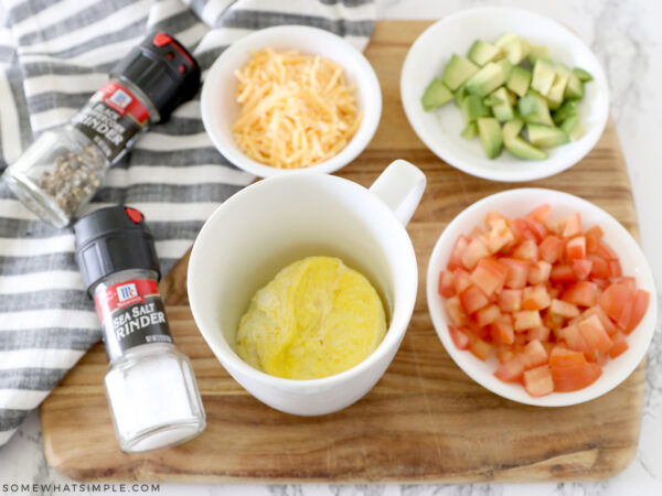 adding to toppings to eggs in a mug