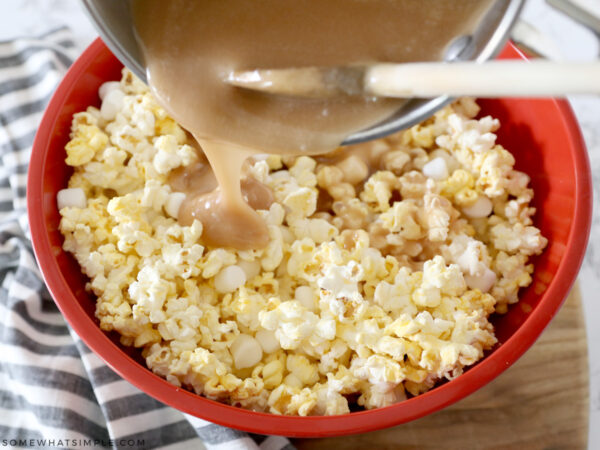 pouring caramel sauce over popcorn