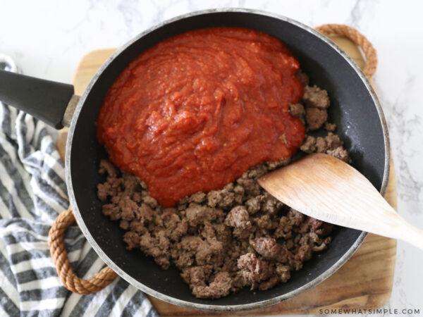 adding pasta sauce to ground beef