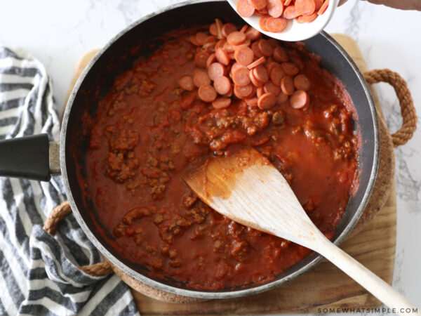 adding pepperoni to meat and sauce