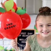 little girl holding red balloon with 2nd grade sign on it