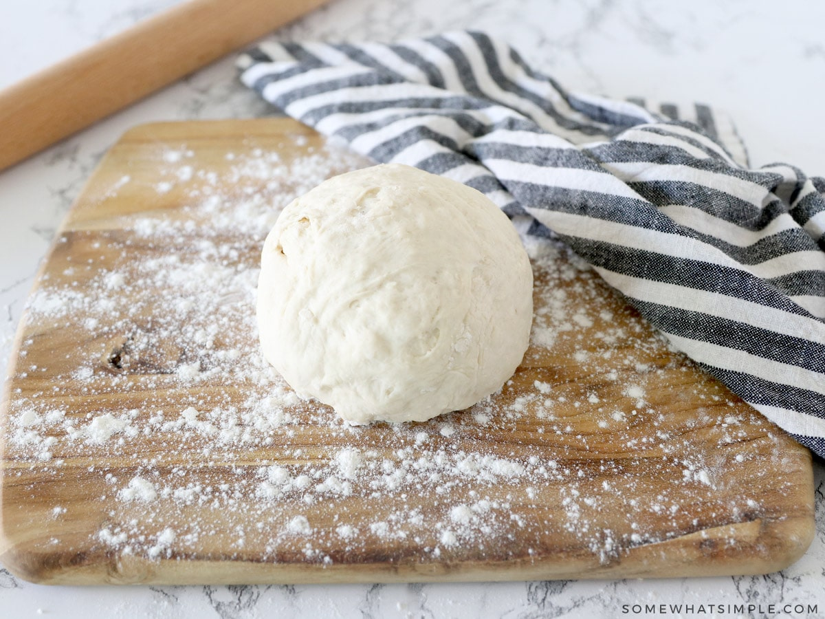 easy pizza dough recipe in a ball on a cutting board