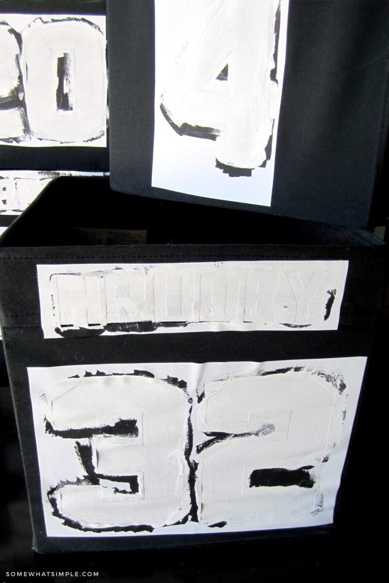painting white numbers on black bins