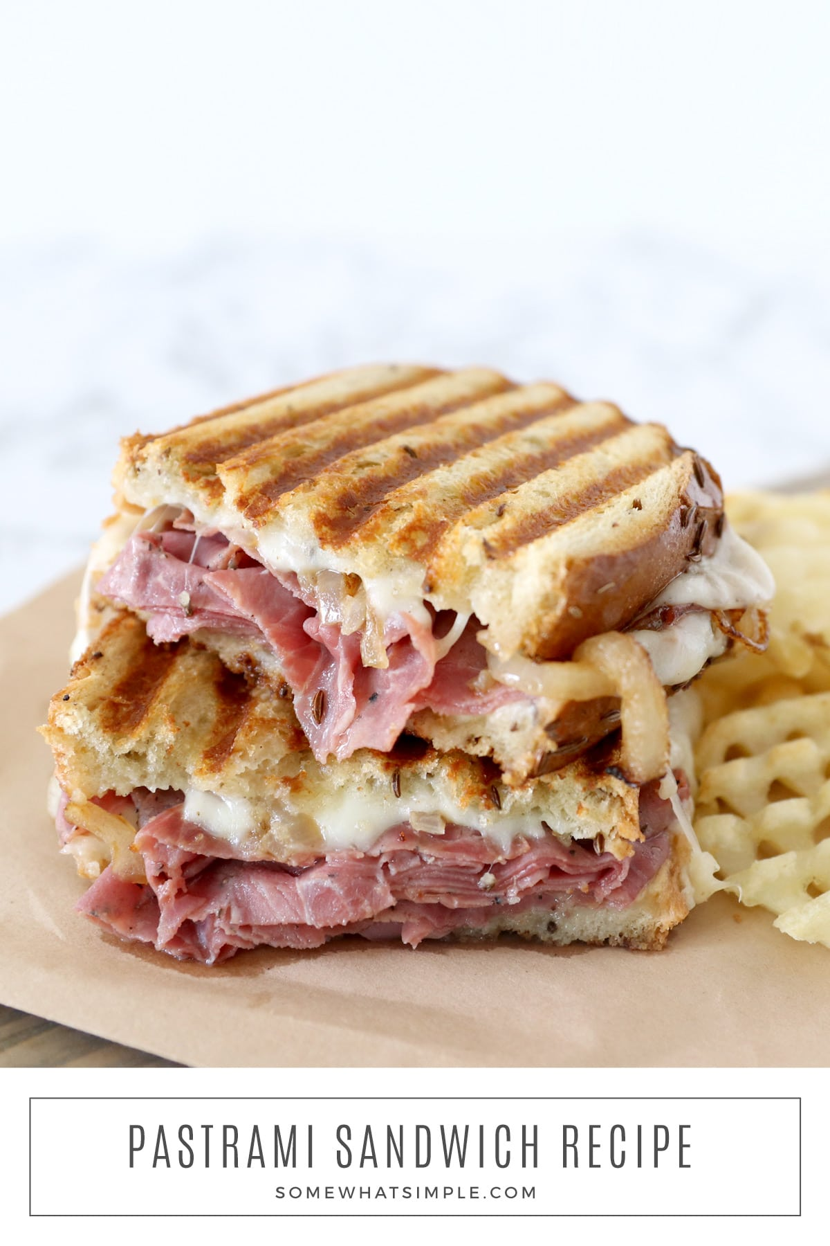 This pastrami sandwich recipe is perfect for those times when you need a quick and easy dinner idea. Delicious bread loaded with hot pastrami, grilled onions, mustard, cheese, and crispy waffle fries, this recipe is easy to make unbelievably tasty! via @somewhatsimple
