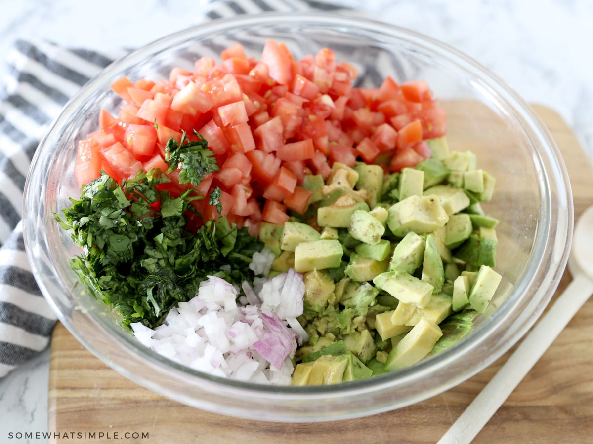 adding all the ingredients of guacamole salsa to a bowl