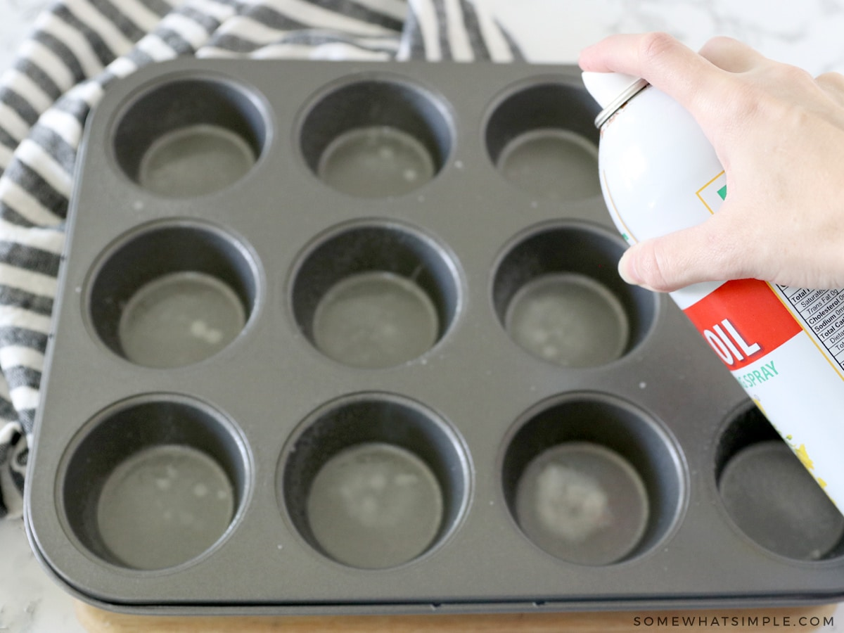 spraying a muffin tin with nonstick spray