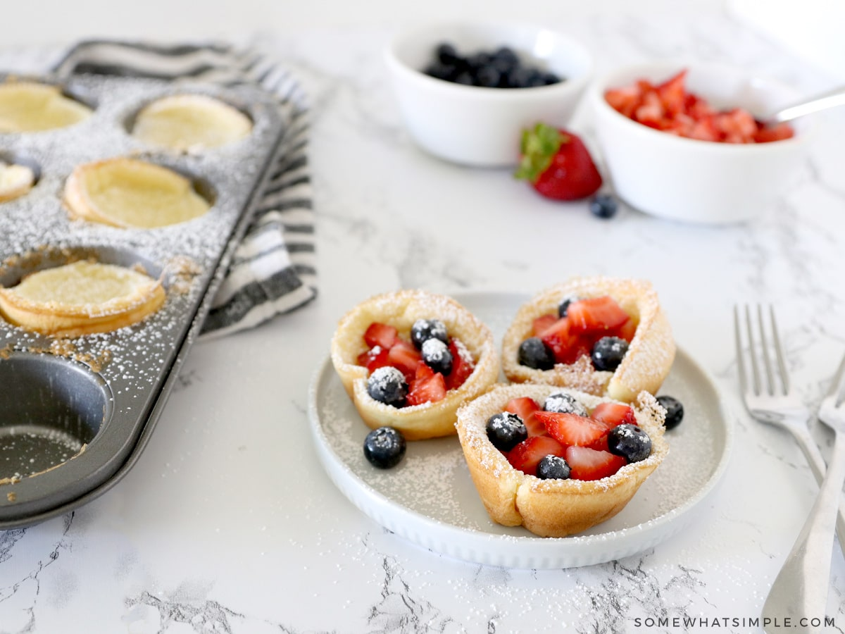 mini dutch baby pancakes topped with berries and sugar