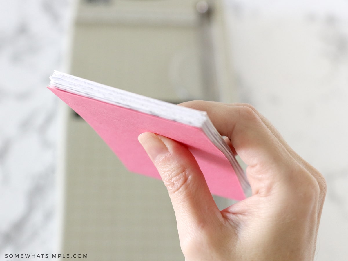 holding a stack of paper