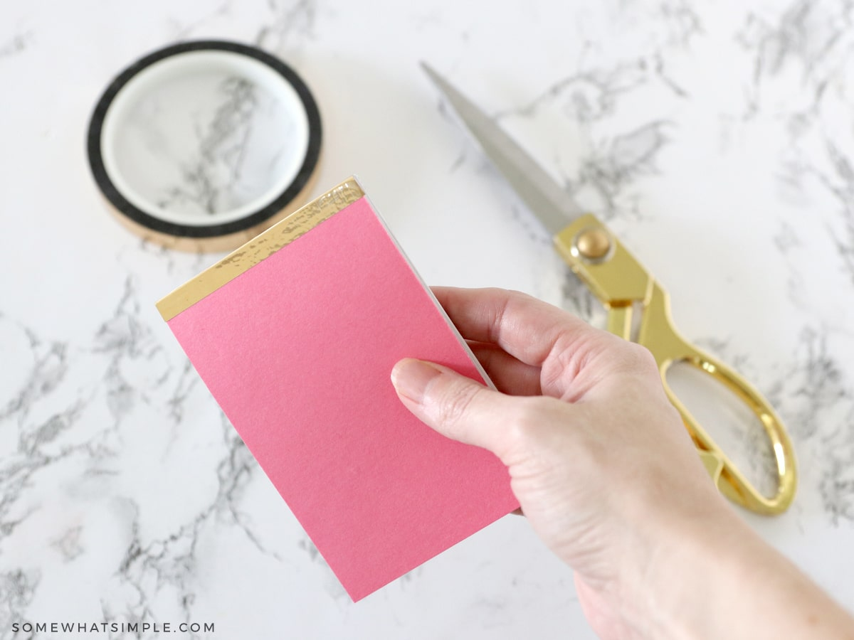 adding gold tape to a notepad