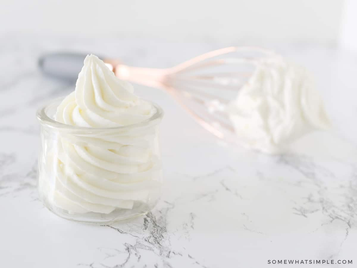 frosting in a small glass jar with a whisk in the background