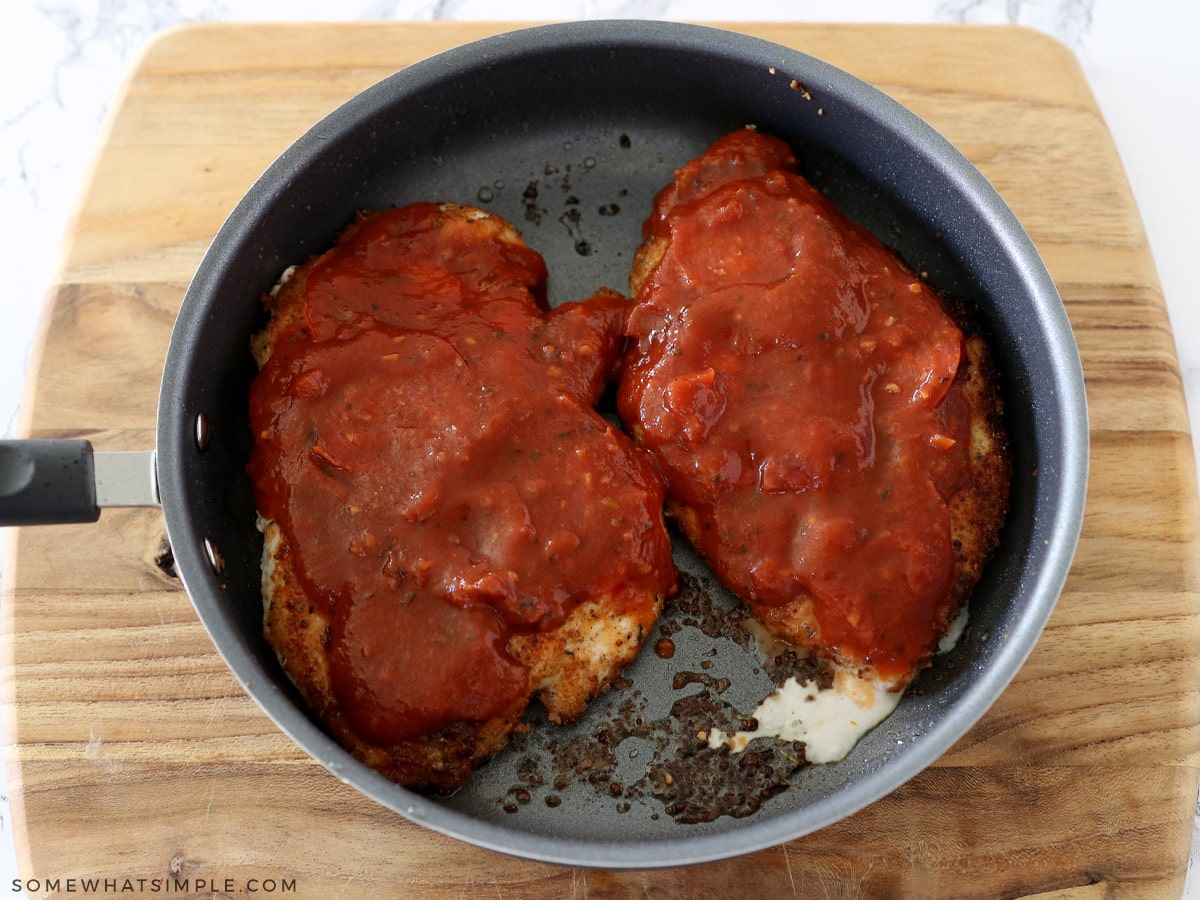 pouring sauce on top of chicken breasts