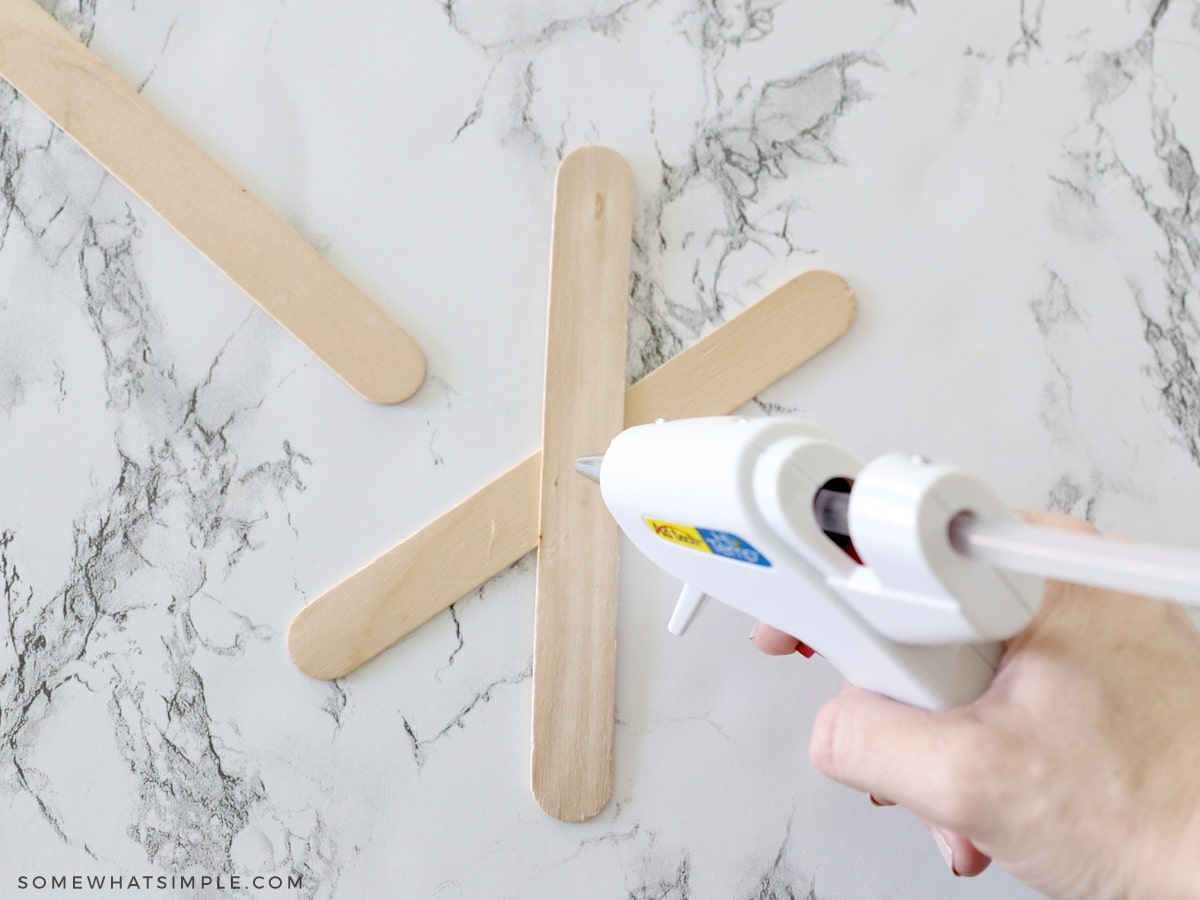 glueing popsicle sticks on top of each other to make a spider web
