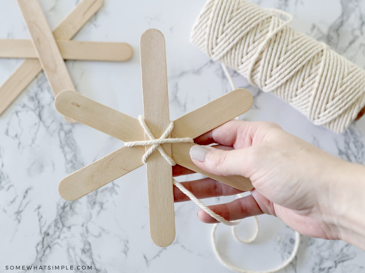 adding yarn to popsicle sticks to make a spider web