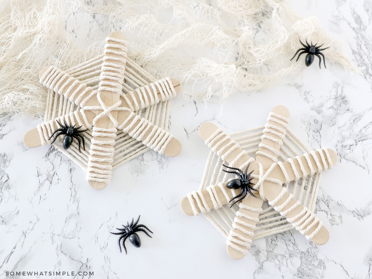 adding plastic spiders to a popsicle stick web