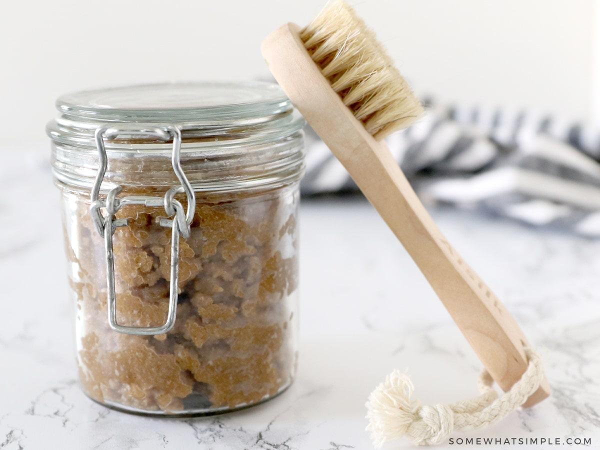 pumpkin sugar scrub in a jar with a bath brush next to it